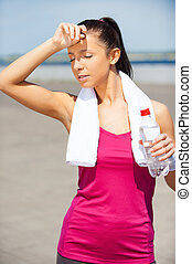 Relaxing after jog. Tired young woman drinking water and keeping eyes closed while standing outdoors