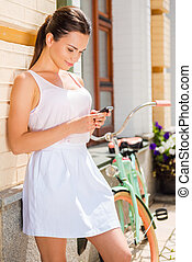 Relaxing after long ride. Beautiful young woman holding mobile phone and smiling while standing near her vintage bicycle