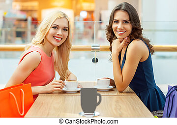 Relaxing after shopping. Two beautiful young women drinking coffee at the restaurant and looking at camera
