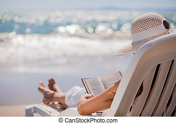 Relaxing and reading at the beach - Young woman on holidays ...