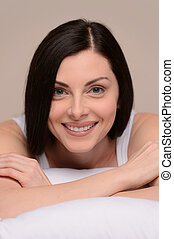 Relaxing at her day off. Beautiful middle-aged women lying on the sofa and smiling at camera