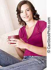 A beautiful young woman relaxing at home on the sofa with a mug of coffee (shallow depth of field used)