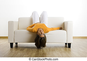 Relaxing at home - Beautiful woman laughing on the couch at...