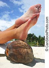 Relaxing Beach Feet - Women's feet resting on a coconut on a...