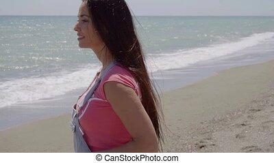 Relaxing beautiful woman walking along beach