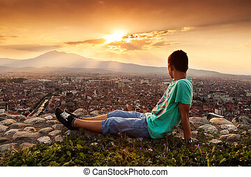 relaxing boy looking to the city