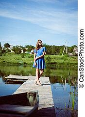 Relaxing brunette young pretty girl in blue dress on bridge