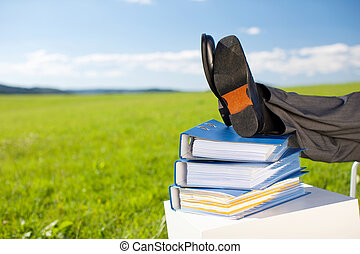 Relaxing businessman with his feet on the stack of books in...