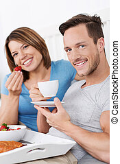 Relaxing couple enjoying breakfast in bed
