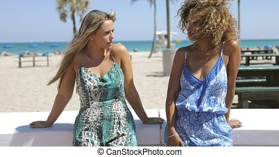 Relaxing diverse women on waterfront - Trendy women in...