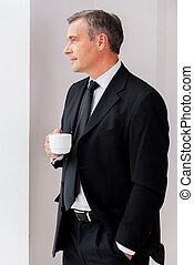 Relaxing during coffee break. Thoughtful mature man in...