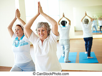 Relaxing exercise - Portrait of two aged females doing yoga...