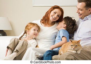 Portrait of happy parents and their children sitting on the sofa with red cat on man?s knees
