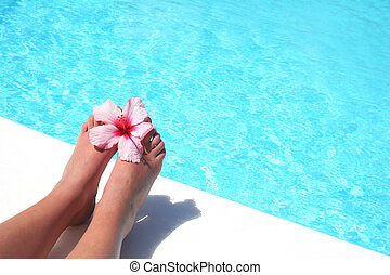 Women's feet by pool with flower