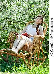 Relaxing girl reading book in bloom garden