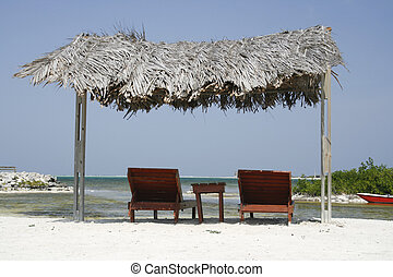 two wooden reclining chairs under a thatched roof on the beach in Bonaire