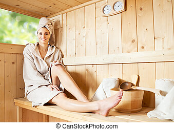 Relaxing in sauna - Young attractive woman smiling and...