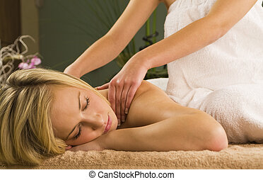 Relaxing Massage - A young woman relaxing at a health spa...