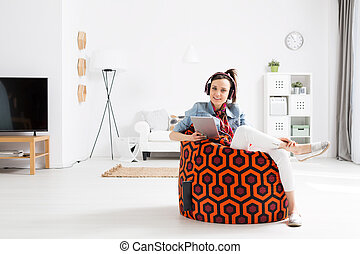 Smiling female student listening to music on a sit sack inside a very bright living room