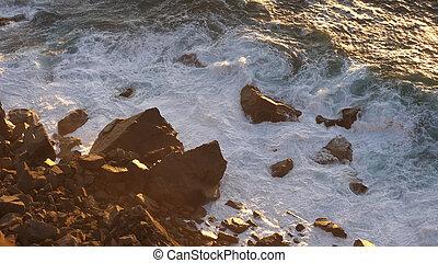 Relaxing ocean waves crashing into rocky shore.