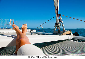 woman lounging on a catamaran sailboat trampoline with her feet propped up and crossed. calm blue ocean and cloudless blue sky are in the background. copy space available