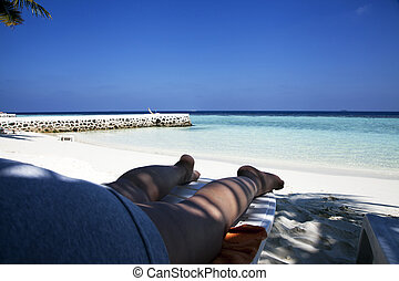 Relaxing on the beach - Woman taking a nap in the shade on a...