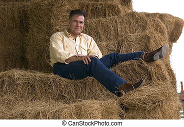 Handsome mature man sitting on a tall stack of bales of hay in the late afternoon.