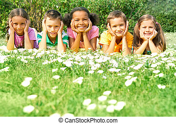 Relaxing outdoors - Portrait of cute kids lying on green ...