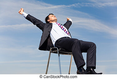 Photo of relaxing businessman sitting on chair and stretching himself on background of blue sky