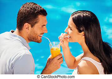 Relaxing poolside together. Top view of beautiful young couple in casual wear drinking cocktail from one glass and smiling while sitting poolside together