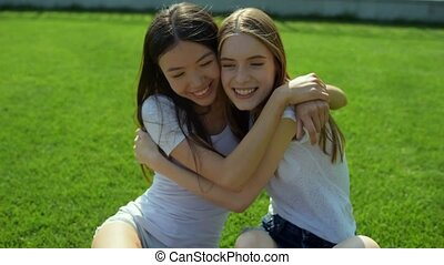 True friendship. Relaxing positive young girls hugging tightly while sitting on the grass