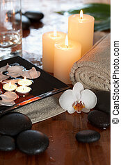 relaxing spa with candles orchids towels and stones on wooden background