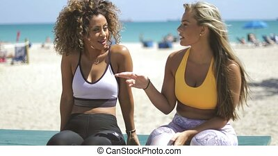 Relaxing sportive women chilling on beach