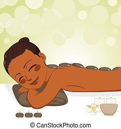 Beautiful African American young woman enjoying relaxing hot stone massage with soft light candles at beauty parlor