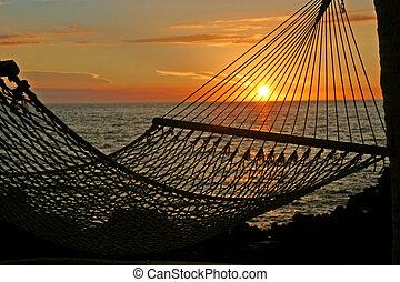 A hammock frames a sunset on the Big Island of Hawaii.