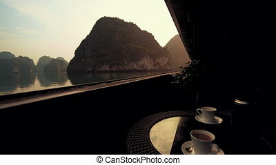 Relaxing with coffee in Ha Long Bay in Vietnam at Sunset