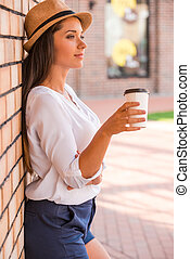 Relaxing with cup of fresh coffee. Side view of thoughtful young woman in funky hat holding cup with hot drink and looking away while leaning at the wall outdoors