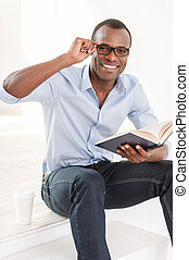 Relaxing with his favorite book. Cheerful young African man in blue shirt holding a book and looking at camera while sitting on stairs with a cup of coffee near him