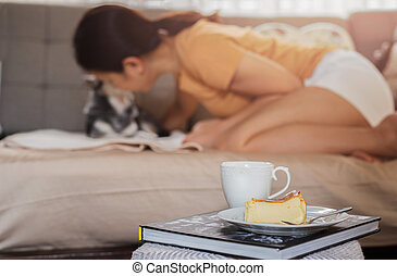 Relaxing woman kissing her dog on sofe with basque burnt cheesecake and coffee on the table.