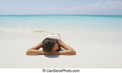 Relaxing woman on beach vacation lying in sand with water ...