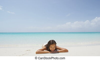 Relaxing woman on beach vacation sunbathing on sand bathing in water. Beautiful girl lying down under the sun tanning in perfect paradise white sand beach and pristine blue ocean background.