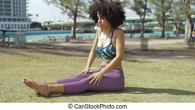 Relaxing woman stretching on lawn in park