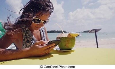 Relaxing young brunette woman wearing sunglasses using cellphone and drinking a cocktail from a coconut in the beach, slow motion. 1920x1080