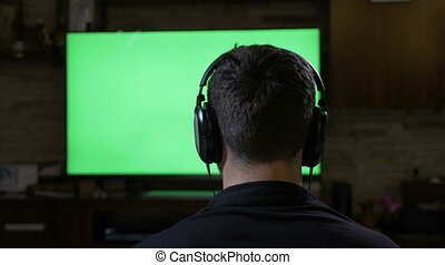 Relaxing young man with headphones playing video game in front of chroma key green screen tv monitor