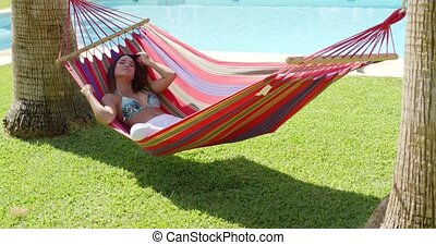Relaxing young woman in colorful hammock