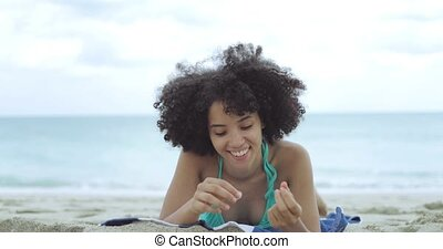Relaxing young woman lying on sandy shore