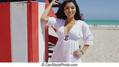 Relaxing young woman on beach in sunlight