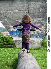 reliability - little girl balancing on a bole