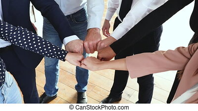 Reliable business team people join fists together in circle...