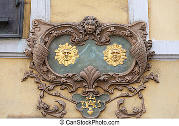 Relief on facade of old building, two suns, Nerudova street...